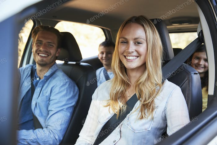 Young family going on holiday in a car look to camera