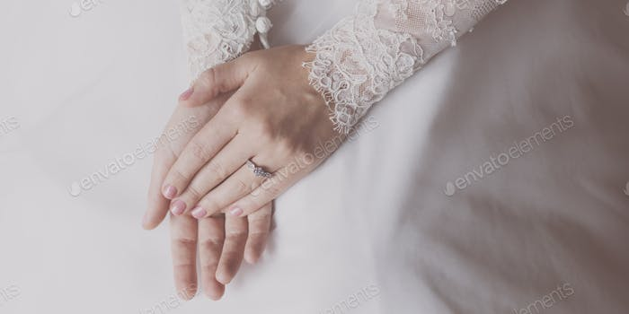 Close up of bride's hands wearing her ring
