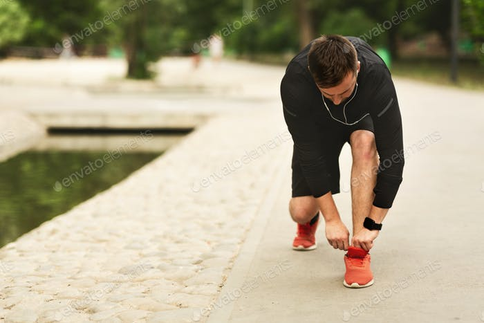 Portrait of Young Man Tying Sports Shoe In Parkland