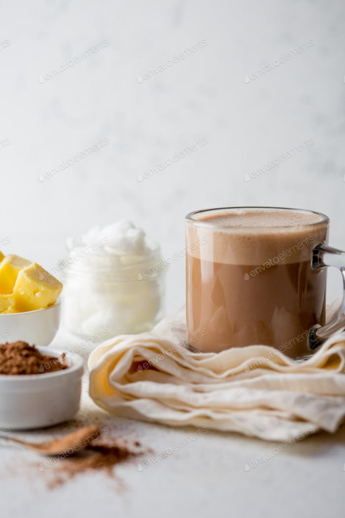 Cup of bulletproof coffe with cacao and ingredients