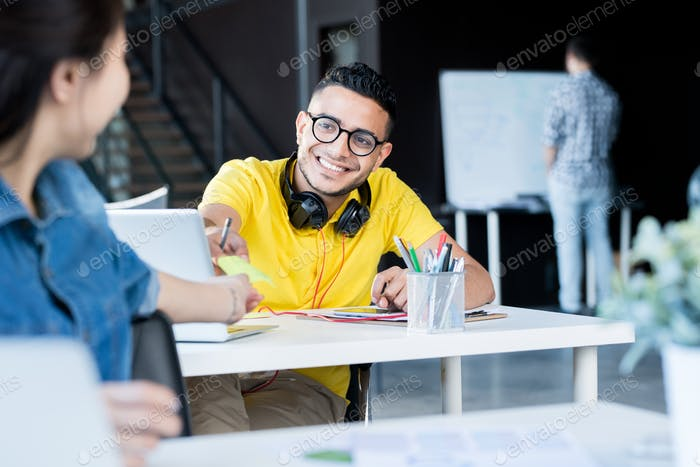 Young People Sharing Notes  in Office