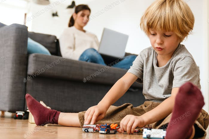 Boy playing on the floor with car toys