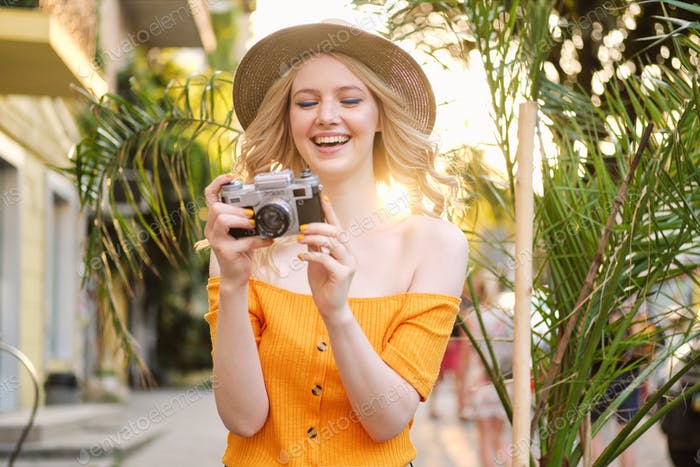 Attractive cheerful blond girl in hat happily taking photo on retro camera on city street