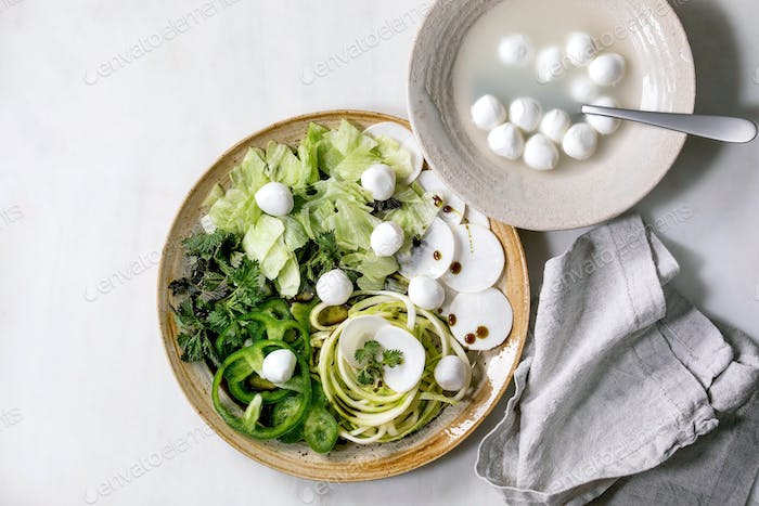 Green raw vegetables and herbs for salad