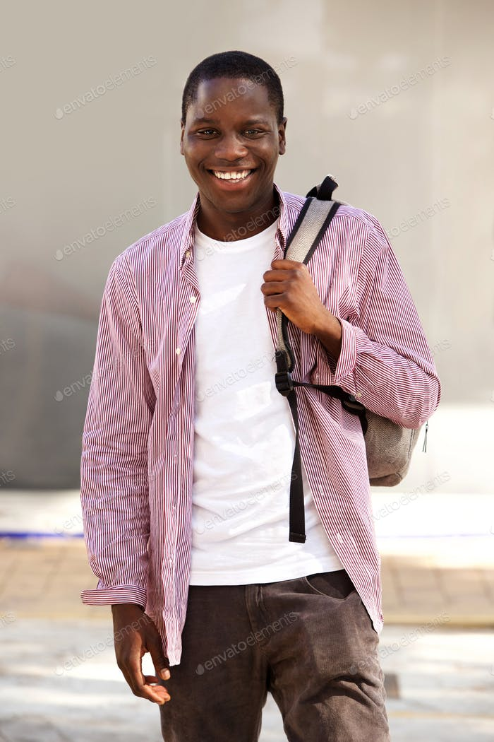 handsome young african student smiling outdoors with bag