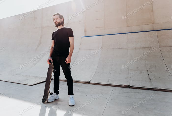 The man dressed in the stylish casual clothes holding skateboard in his hand stands in a skate park