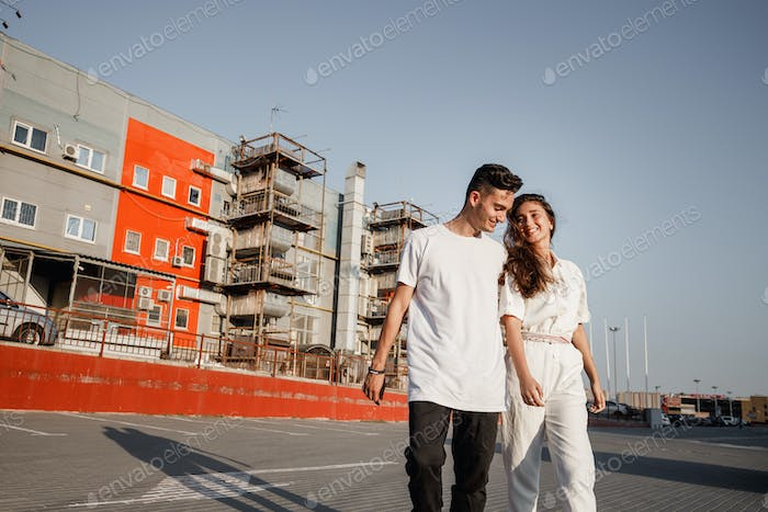 Young guy and girl are walking on the square on the background of urban building in the warm day