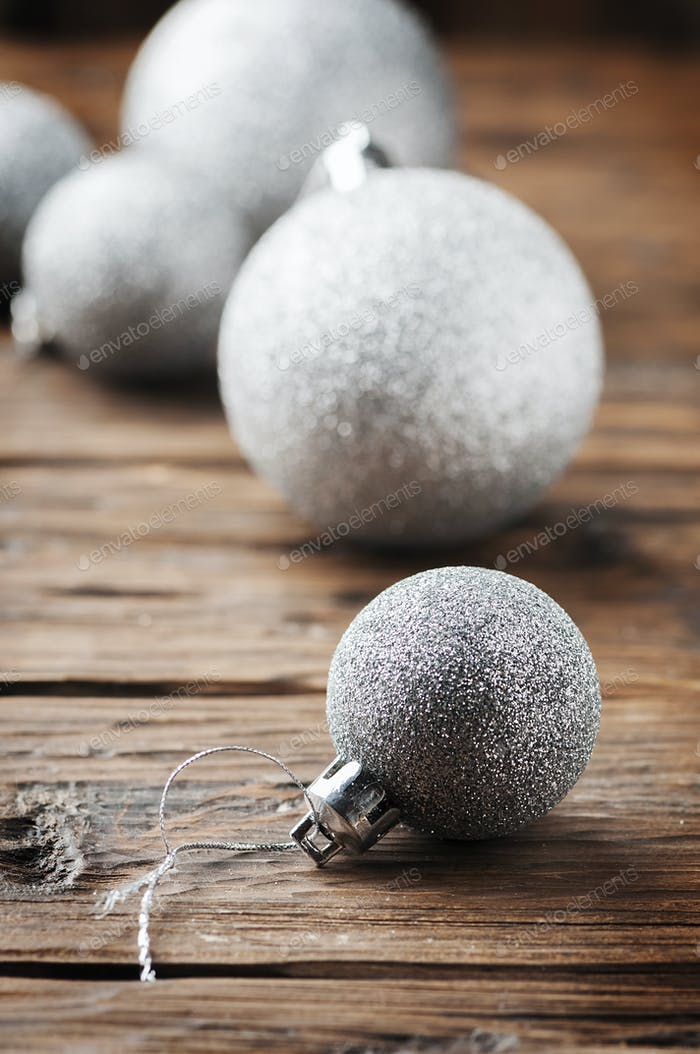 Christmas card with silver balls on the wooden table