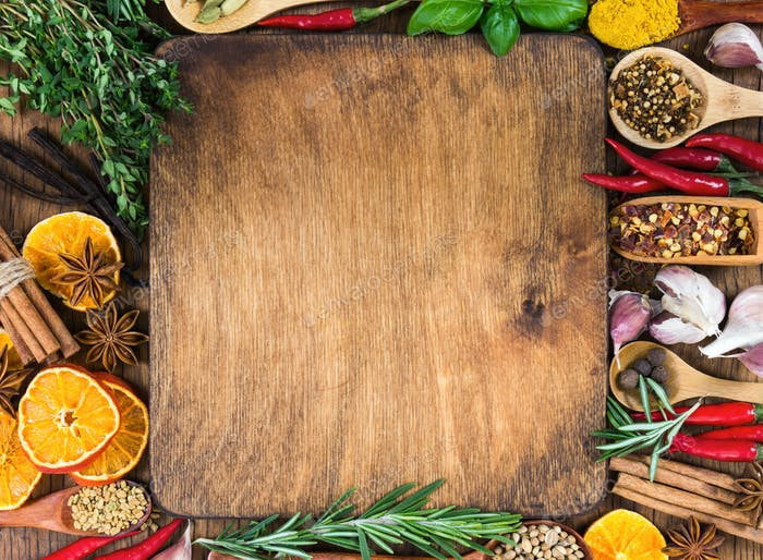 Various spices, seasonings and herbs on wooden background