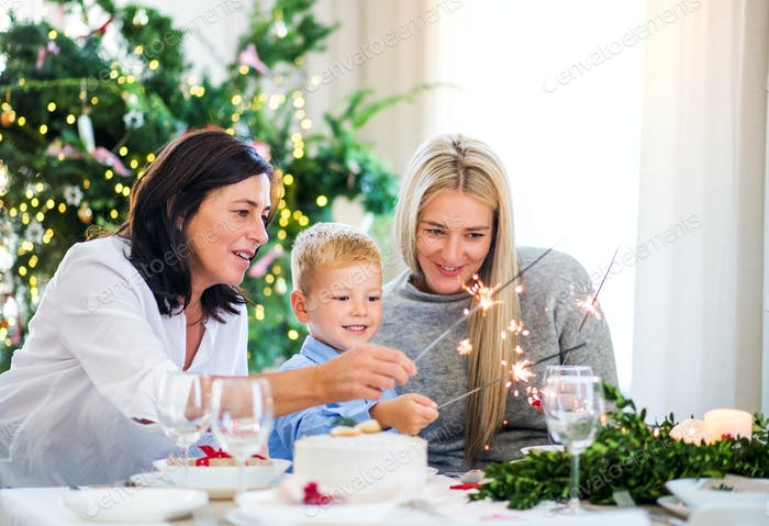 A small boy with mother and grandmother holding sparkle at Christmas time.