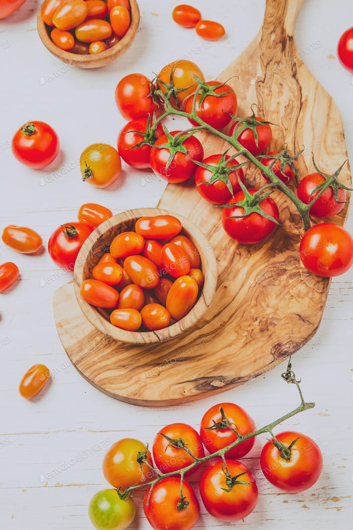 Fresh cherry tomatoes on olive wooden bowls and board, white background, top view.