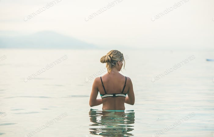 Young woman standing in still sea waters in Alanya, Turkey