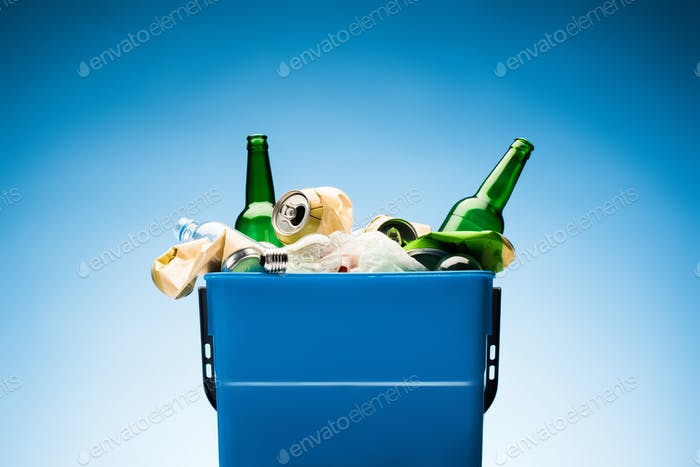 various trash in trash bin on blue