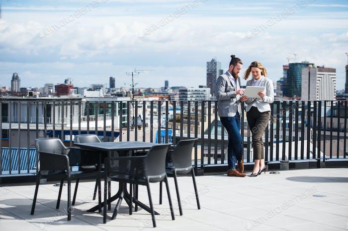 Dos jóvenes empresarios con tableta de pie en una terraza fuera de la oficina, trabajando