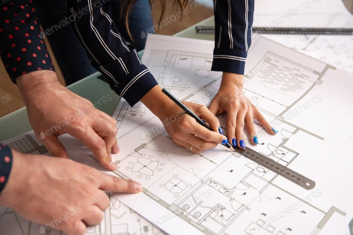Close up with the hands of two architects sketching something in a house plan