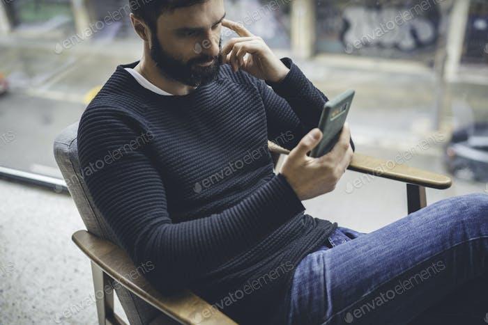 Alegre hombre caucásico con jersey negro usando la aplicación de teléfono móvil para blogs móviles.