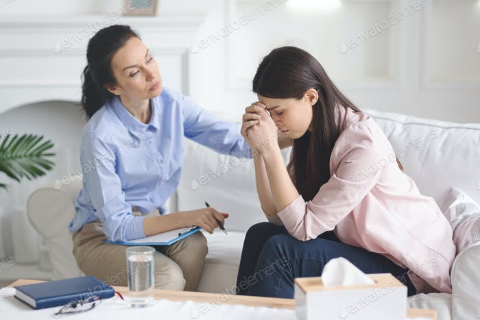 Therapist comforting her depressed crying woman patient