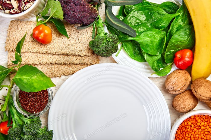 Auswahl Lebensmittel reich an Ballaststoffen auf weißem Holzhintergrund um leere Platte
