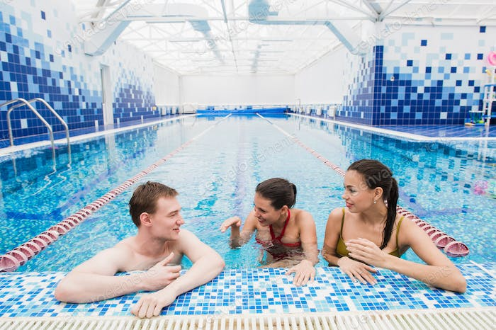 Young adults having fun talking in swimming pool indoors