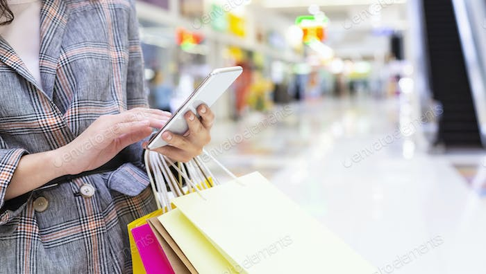 Shopping time. Unrecognizable woman with cellphone and purchases