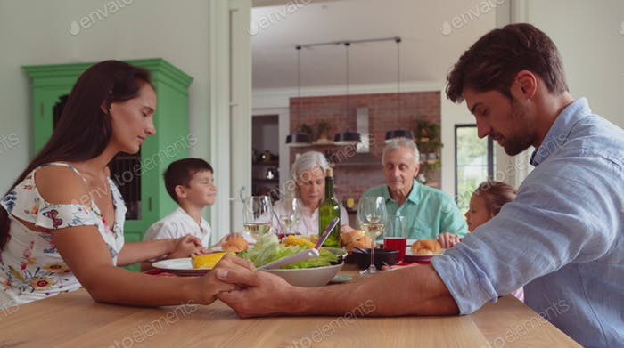 Front view of multi-generation Caucasian family praying before having food on dining table at home
