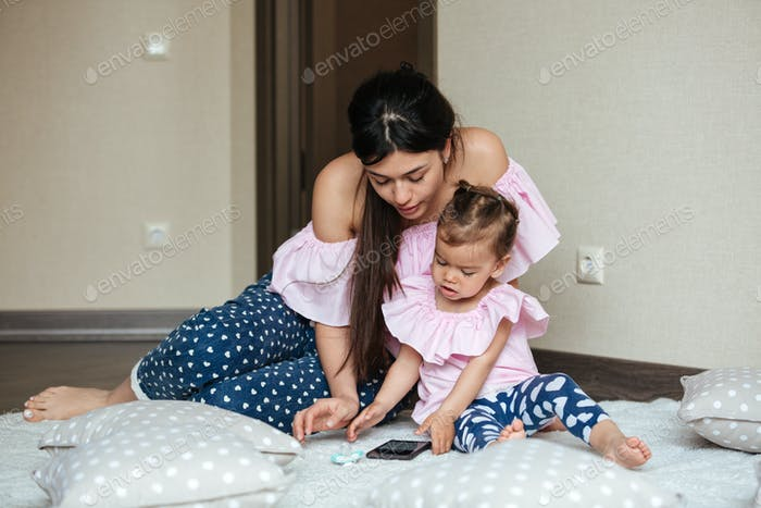 Concentrated young mother with her little daughter chatting by phone