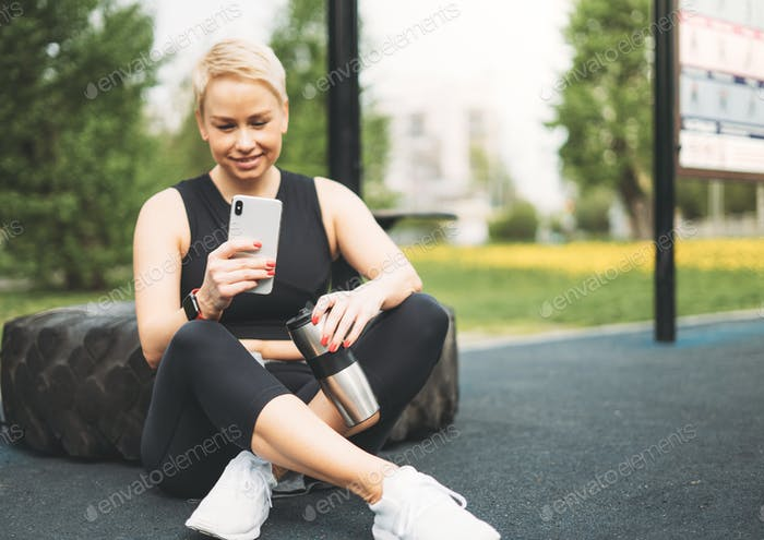 Attractive blonde young woman in sport resting with mobile
