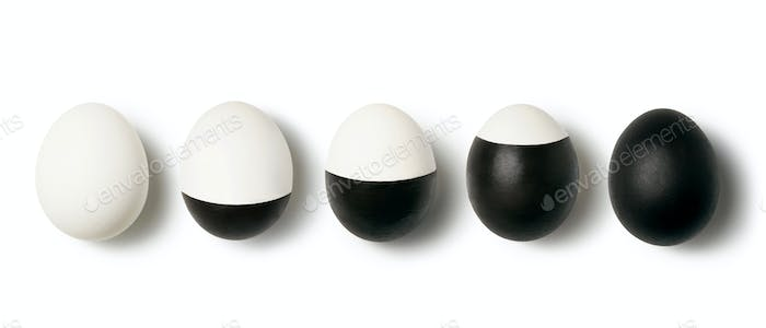 White and black colored eggs on a white background with copy space. Concept of changing life. Flat