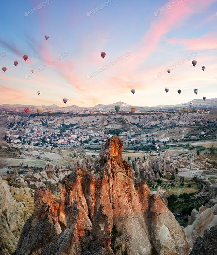 Balloons over rocks of Cappadocia in early morning