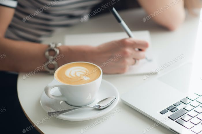 Close up picture of woman's hands and a cup of cappuccino. Lady is writing in her notebook with
