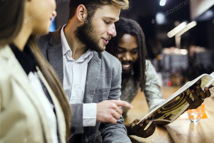 Коллеги читают статьи в пабе