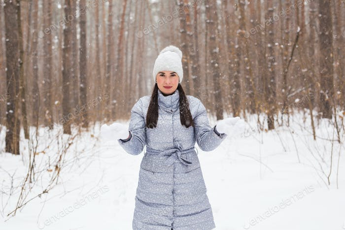 Winter, season and people concept - Woman in grey coat and white hat walking in winter park and