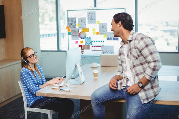 Graphic designers interacting with each other in conference room