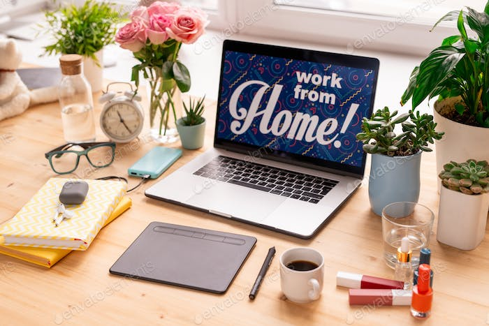 Work from home notice on display of laptop surrounded by books, pad, etc