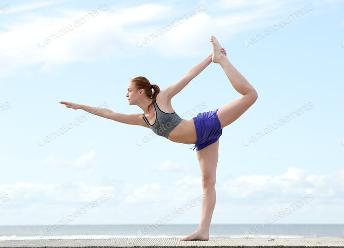 Young woman balancing on one leg in yoga position