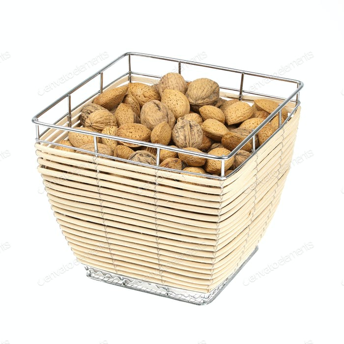 Almonds and walnuts in a food basket isolated on white