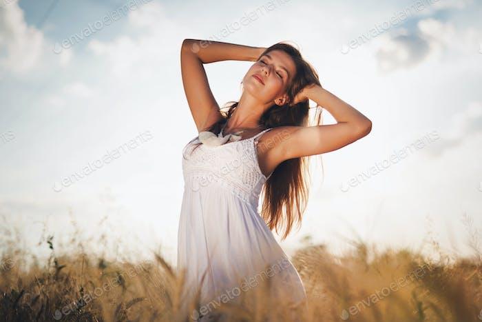Schöne unbeschwerte Frau auf Feldern