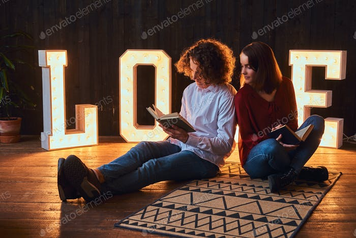 Young student couple in a room decorated with voluminous letters with illumination.