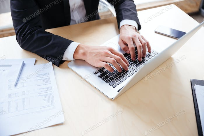 Hands of young businessman working using laptop in office