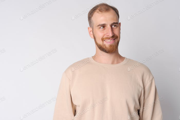 Face of happy young bearded man thinking and looking up