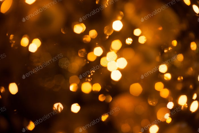Christmas blurred golden lights out of focus on the tree, festive christmas glowing bokeh background