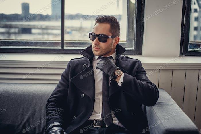 Ein Mann mit Sonnenbrille und schwarzen Handschuhen.