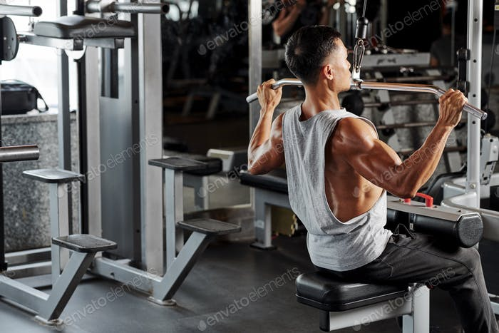 Man exercising in pull down machine
