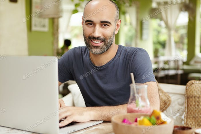 People, lifestyle and modern technology. Outdoor portrait of happy handsome man sitting at cafe tabl