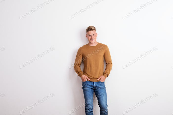 Portrait of a happy young man standing in a studio, hands in pockets.