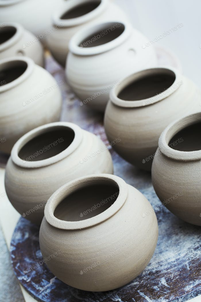 A row of handthrown pots, vases with round tops.