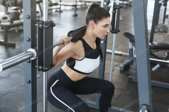 Young woman doing exercises with barbell in gym