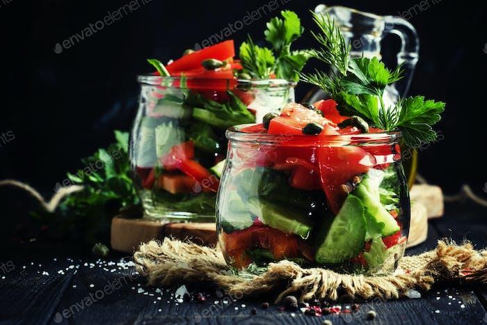 Veganer Salat mit Gemüse, Kräutern, Kapern und Olivenöl in Gläsern