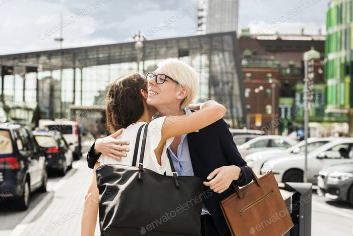 Two women embracing in parking lot