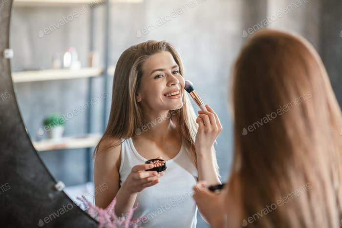 Beauty and makeup. Pretty young woman applying blusher on her face near mirror at home